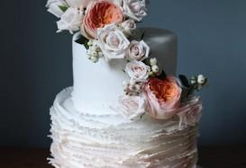 Signature ruffle wedding cake with fresh floral arrangement